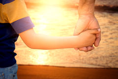 parent-child-holding-hands-beach-96265808